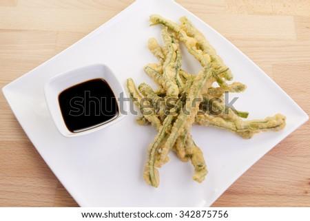 Tasty Green Beans Tempura, also called peixinhos da horta, and dipping sauce - stock photo