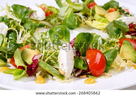 Tasty green salad. Close-up of green salad with mozzarella, tomatoes, zucchini, mash-salad, frisee  - stock photo