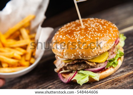 Tasty grilled beef burger with lettuce, ketchup, onion rings, chili ...