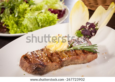 Tasty grilled beef steak topped with a twirled knob of butter and a sprig of fresh rosemary and served on a white plate, close up view - stock photo