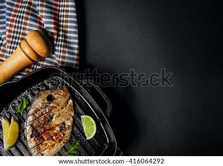 Tasty grilled fish (Vomer) on the barbeque pan with dill and lime, pepper mill.Black background free space - stock photo