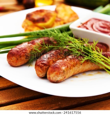 tasty grilled meat sausages on dish - stock photo
