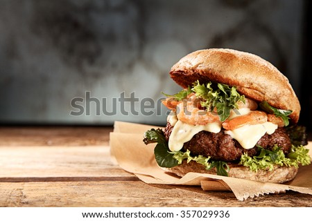 Tasty grilled prawn and beef burger with lettuce and mayonnaise served on pieces of brown paper on a rustic wooden table of counter, with copyspace - stock photo