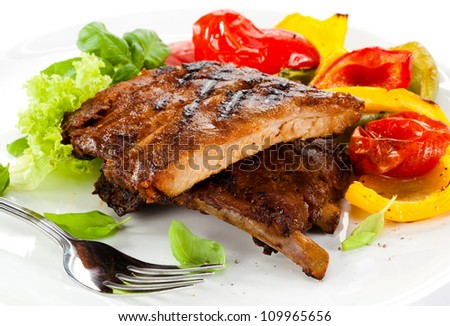 Tasty grilled ribs with vegetables - stock photo