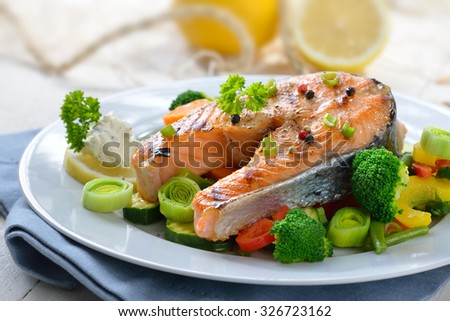 Tasty grilled salmon steak on mixed colorful vegetables, lemons and a fishing net in the background