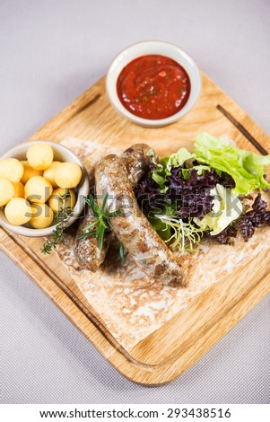 Tasty grilled sausages with vegetables and sauce close up on wooden board - stock photo