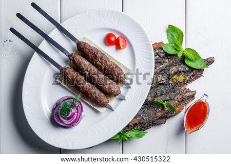 Tasty grilled shish kebab with sauce and greens - stock photo