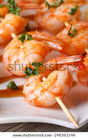 tasty grilled shrimp on wooden skewers macro on a plate. vertical  - stock photo