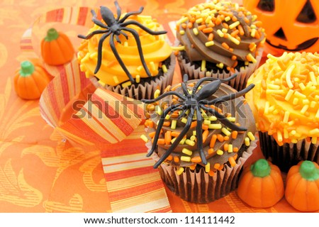 Tasty Halloween cupcakes and candy on orange patterned background - stock photo