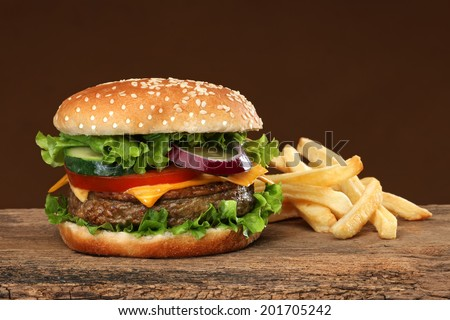 Tasty hamburger and french fries on wood background.
