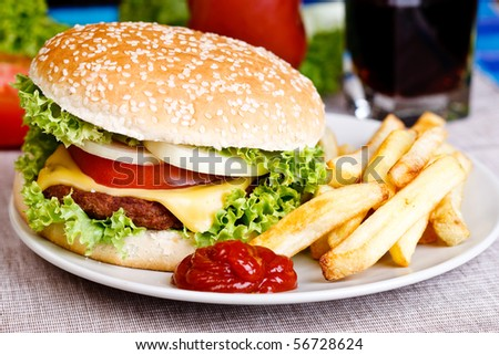 Tasty hamburger with fries and soda in the background. - stock photo