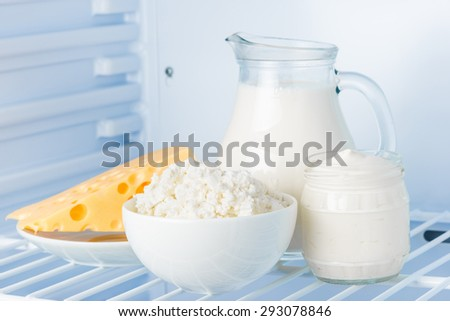 tasty healthy dairy products in the refrigerator: sour cream in the bank, cottage cheese in  bowl,  cheese  and milk in a jar - stock photo