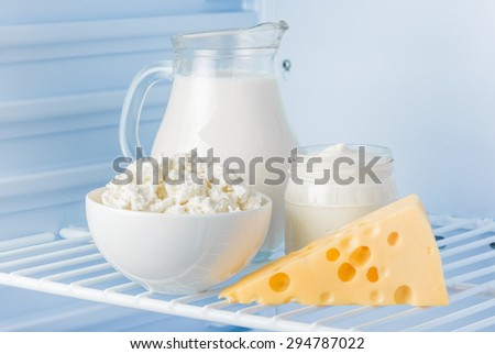 tasty healthy dairy products in the refrigerator: sour cream in the bank, cottage cheese in  bowl,  cheese  and milk in a jar