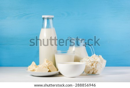 tasty healthy dairy products on a white table on a blue background: sour cream in a white bowl, cottage cheese in bowl,  butter on a saucer, milk in a jar, glass bottle and in a glass