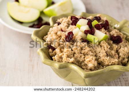 Tasty heart healthy oatmeal breakfast cereal with apples and cranberries on top - stock photo