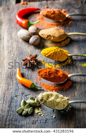 Tasty herbs and spices on old spoons - stock photo