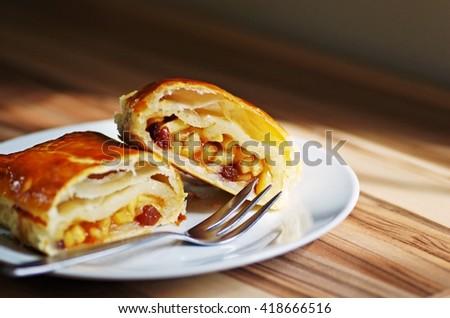 Tasty homemade apple strudel dessert on white plate on wooden rustic table.  - stock photo