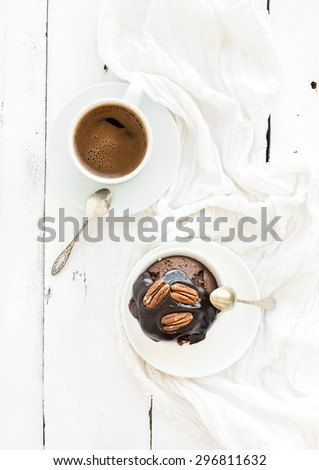 Tasty homemade brown muffin with chocolate ganache icing and pecan nuts, cup of black coffee. Top view - stock photo
