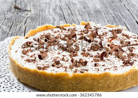 tasty homemade cheesecake pie banoffee with bananas, whipped heavy cream on the old rustic table, classic recipe, horizontal top view, macro - stock photo