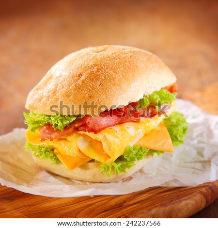 Tasty homemade hamburger filled with slices of pork ham, cheese and green fresh salad or lettuce, served on a paper, on a rustic wooden table - stock photo