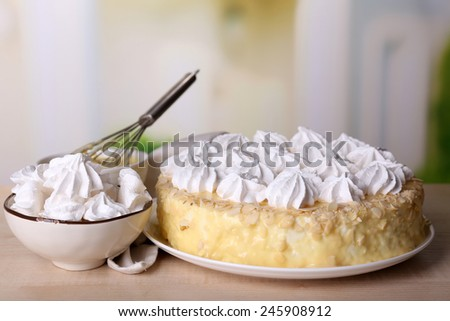 Tasty homemade meringue cake on wooden table, on light background - stock photo