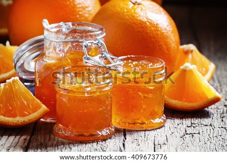 Tasty homemade orange jam and fresh oranges, vintage wooden background, selective focus - stock photo