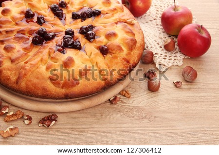 tasty homemade pie with jam and apples, on wooden table - stock photo