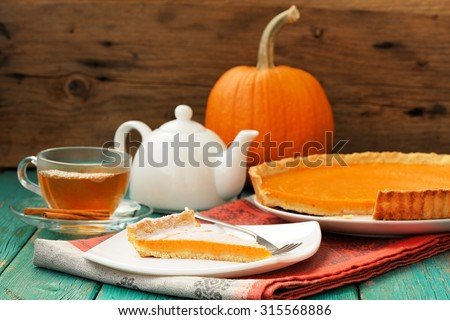 Tasty homemade pumpkin pie with cut piece, tea in glass cup, white teapot and fresh pumpkin on turquoise table - stock photo