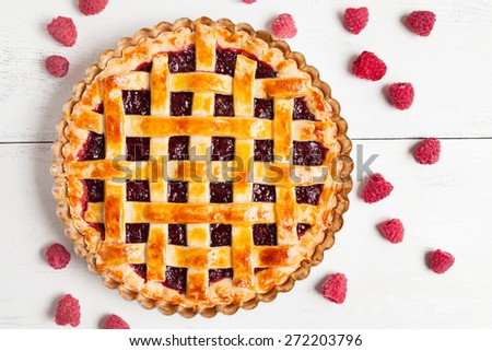 Tasty homemade raw raspberry pie greased with egg yolk with jam on white rustic kithen table background - stock photo