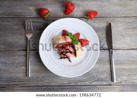 Tasty homemade strudel with ice-cream, fresh strawberry and mint leaves on plate, on wooden background - stock photo