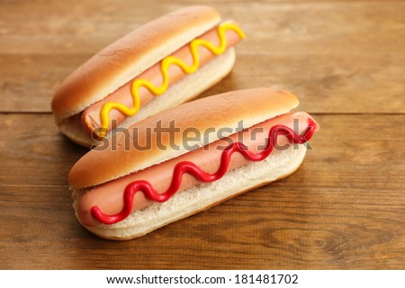 Tasty hot dogs on wooden table