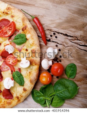 tasty hot pizza with ham, bacon, tomatoes, mushrooms and cheese on wood background - stock photo