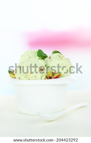 Tasty ice cream scoops in bowl, on wooden table