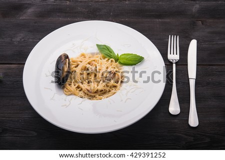 tasty italian pasta with basil leaf and mussels - stock photo