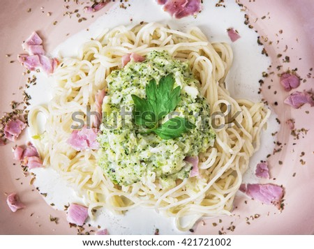 Tasty italian spaghetti with broccoli sauce, ham and parsley on the pink plate. International cuisine. Food theme. One portion. - stock photo