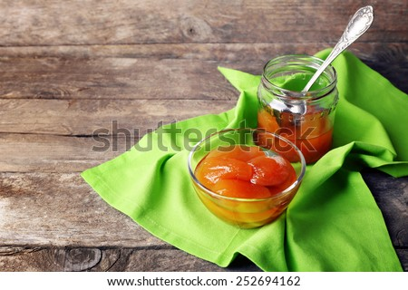 Tasty jam in bowl and jar with napkin on wooden background - stock photo