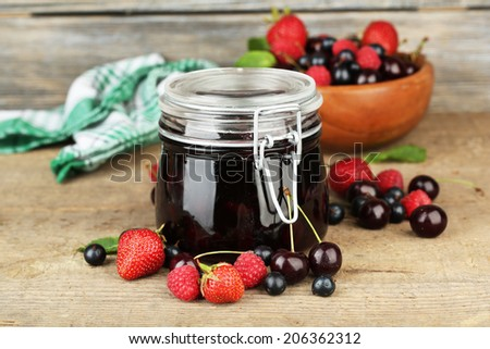 Tasty jam with berries in glass jar on wooden table - stock photo
