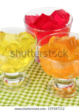 Tasty jelly cubes in bowls on table on white background - stock photo