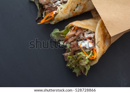 tasty kebab with beef and vegetables on black background