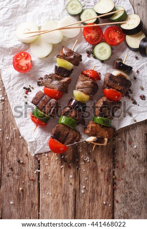 Tasty kebab with vegetables on skewers close-up on the table. Vertical view from above - stock photo
