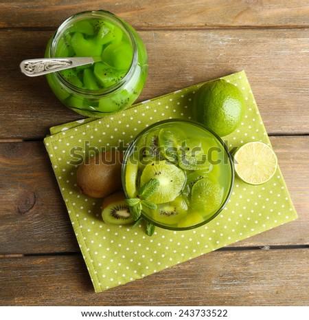 Tasty kiwi jam in glass bowl on wooden background - stock photo