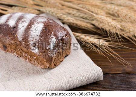 Tasty loaf of healthy wholegrain bread on a cloth with fresh ripe wheat alongside in a conceptual image - stock photo