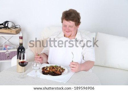 Tasty lunch for fat man, on home interior background   - stock photo