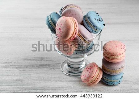 Tasty macaroons in glass dish on wooden table - stock photo