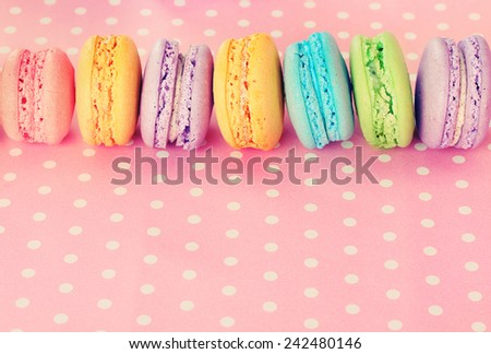Tasty macaroons on pink polka dot background - stock photo