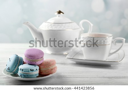 Tasty macaroons with tea on wooden table - stock photo