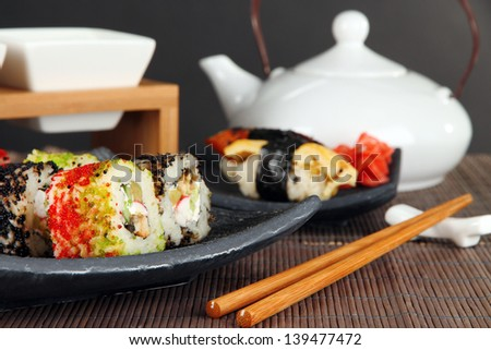 Tasty Maki sushi - Roll on green leaf on table on gray background