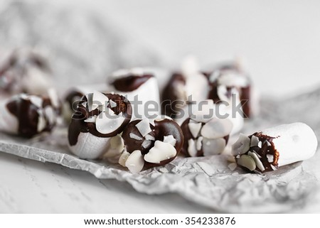 Tasty marshmallows with chocolate on paper, close up