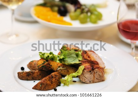 Tasty meat and baked potato on white plate - stock photo