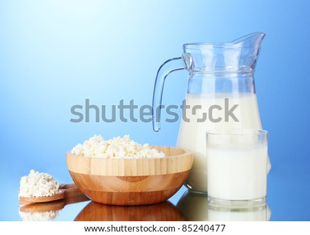 Tasty milk and cottage cheese on  blue background